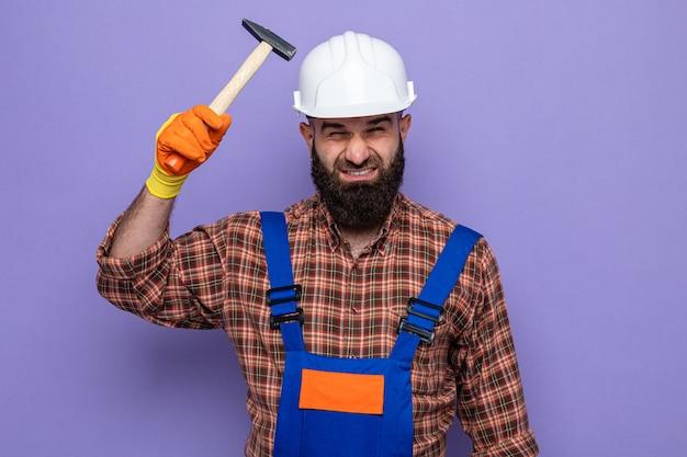 Bebaarde bouwman in bouwuniform en veiligheidshelm met rubberen handschoenen die een hamer vasthoudt en naar de camera kijkt, verward en erg angstig over een paarse achtergrond