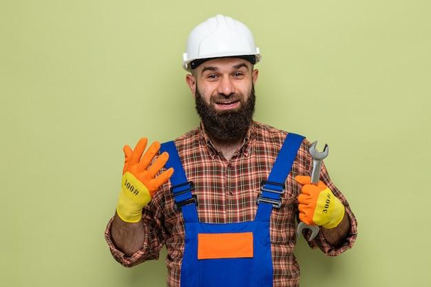 Bebaarde bouwman in bouwuniform en veiligheidshelm met rubberen handschoenen die een moersleutel vasthoudt en er blij en opgewonden uitziet met het optillen van de arm