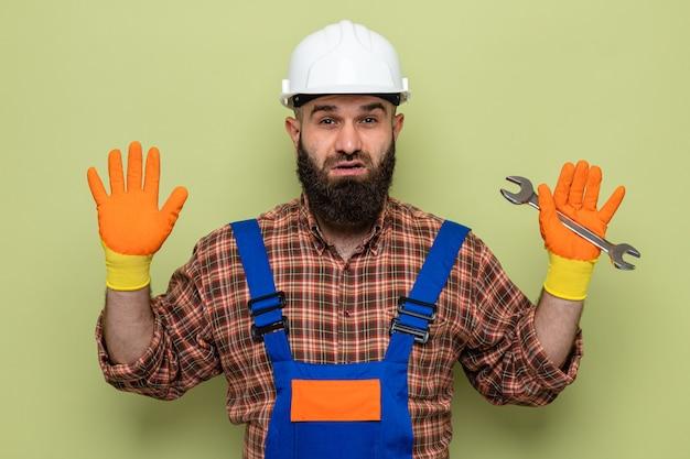 Bebaarde bouwman in bouwuniform en veiligheidshelm met rubberen handschoenen die een sleutel vasthoudt en er verward uitziet met opgeheven armen raising