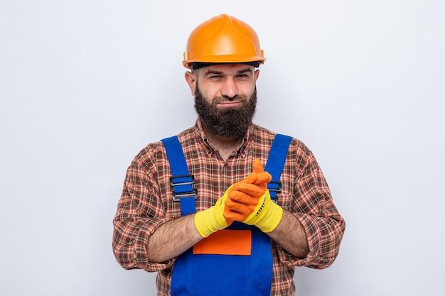 Bebaarde bouwman in bouwuniform en veiligheidshelm met rubberen handschoenen die er blij en tevreden uitziet terwijl hij de handen wrijft
