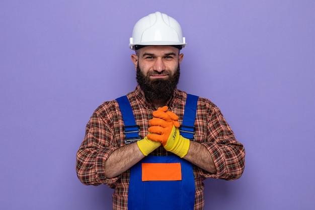 Bebaarde bouwman in bouwuniform en veiligheidshelm met rubberen handschoenen die er gelukkig en zelfverzekerd uitziet en elkaars hand vasthoudt