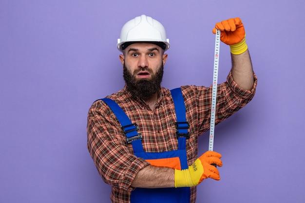 Bebaarde bouwman in bouwuniform en veiligheidshelm met rubberen handschoenen die er verbaasd uitziet met het gebruik van meetlint