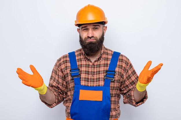 Bebaarde bouwman in bouwuniform en veiligheidshelm met rubberen handschoenen die er verward uitziet en armen naar de zijkanten spreidt zonder antwoord