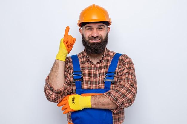 Bebaarde bouwman in bouwuniform en veiligheidshelm met rubberen handschoenen die er vrolijk lachend uitziet met wijsvinger