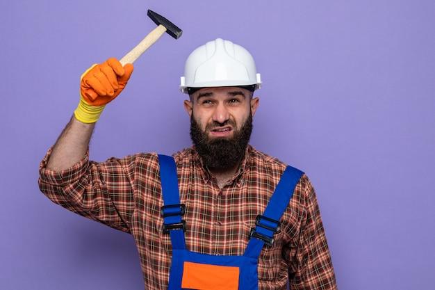 Bebaarde bouwman in bouwuniform en veiligheidshelm met rubberen handschoenen die met een hamer zwaait en er verward uitziet over een paarse achtergrond