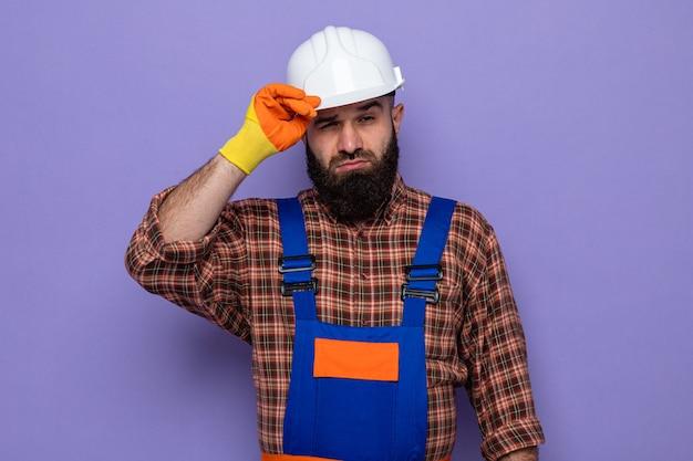 Bebaarde bouwman in bouwuniform en veiligheidshelm met rubberen handschoenen die met een zelfverzekerde uitdrukking zijn helm aanraakt