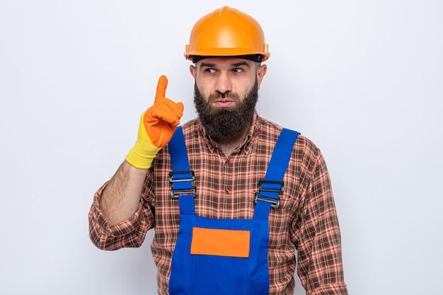 Bebaarde bouwman in bouwuniform en veiligheidshelm met rubberen handschoenen die opzij kijkt verbaasd en laat zien dat wijsvinger een nieuw idee heeft