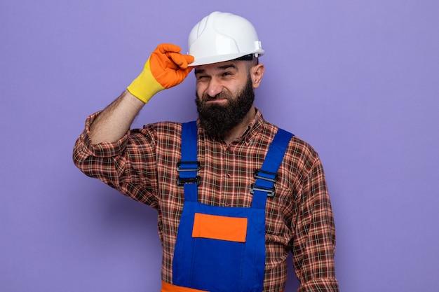 Bebaarde bouwman in bouwuniform en veiligheidshelm met rubberen handschoenen die verward en ontevreden opzij kijkt