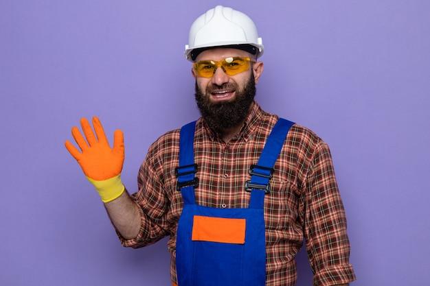 Bebaarde bouwman in bouwuniform en veiligheidshelm met rubberen handschoenen kijkend naar camera glimlachend vrolijk zwaaiend met hand over paarse achtergrond