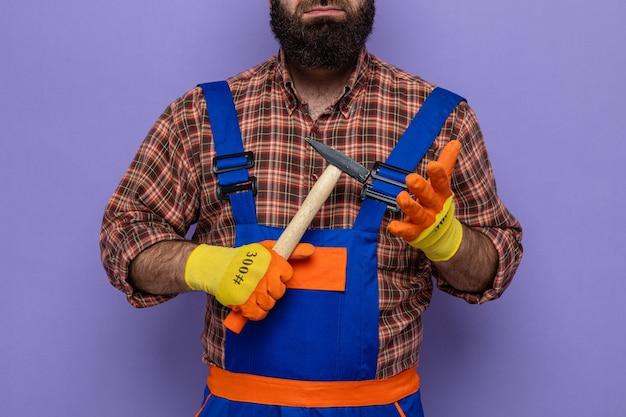 Bebaarde bouwman in bouwuniform en veiligheidshelm met rubberen handschoenen met een hamer op een paarse achtergrond