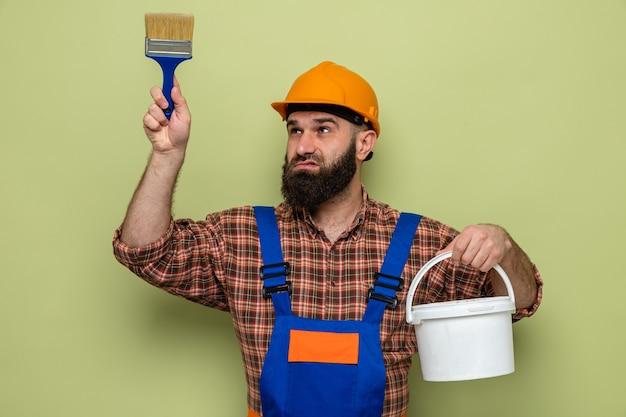 Bebaarde bouwman in bouwuniform en veiligheidshelm met verfemmer en borstel die verward opkijkt over groene achtergrond