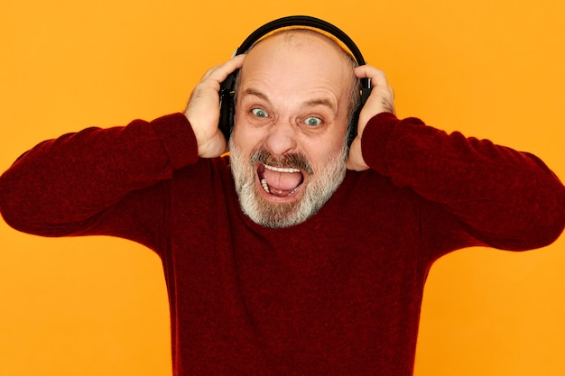Bebaarde boze woedende gepensioneerde man in gebreide trui mond wijd openen woedend met slecht nieuws luisteren naar sport radiostation via draadloze bluetooth-koptelefoon, hardop schreeuwen