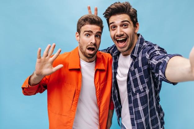 Bebaarde brunet man in geruit hemd neemt selfie en zet konijnenoren naar zijn vriend. kerel in oranje jasje wil geen foto maken.