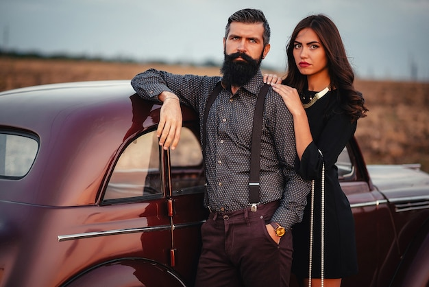 Bebaarde brunette man in een shirt en broek met bretels knuffelt een slank jong meisje met lang haar in een zwarte korte jurk in de buurt van een bruine retro auto op de achtergrond van het veld