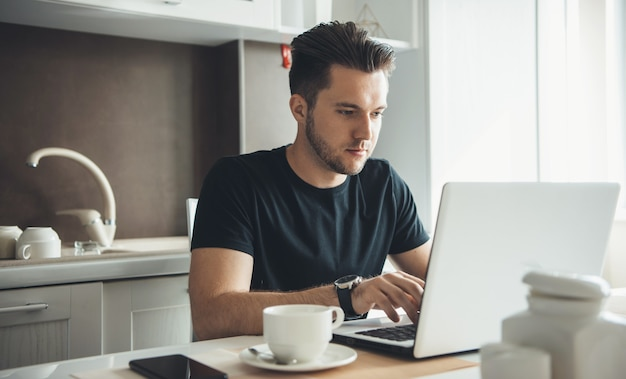 Bebaarde brunette man is freelancen op de laptop thuis in de keuken terwijl hij een kopje koffie drinkt