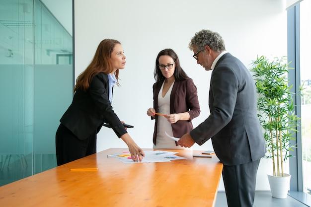Bebaarde ceo van middelbare leeftijd in glazen die met managers werken en verslag lezen