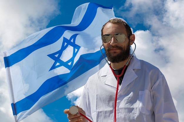 Bebaarde charmante amerikaanse joodse dokter man in witte keppeltje (hoed, keppel, joodse hoed) dragen van een zonnebril, jas en stethoscoop op israël vlag achtergrond. dubbele blootstelling van russische knappe man