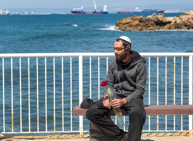 Bebaarde charmante amerikaanse joodse man in witte keppeltje (kippa, joodse hoed) met zonnebril, capuchonjasje met roos, wachtend op zijn vrouw op het zeestrand. russisch kaukasisch modemannetje kijkt naar de zijkant