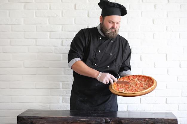 Bebaarde chef-kok bereidt maaltijden aan tafel in de keuken