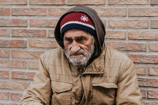 Bebaarde dakloze man voor bakstenen muur