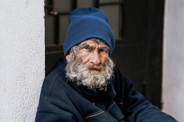 Bebaarde dakloze man voor de deur
