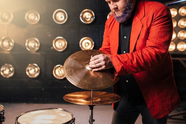 Bebaarde drummer in rood pak op het podium