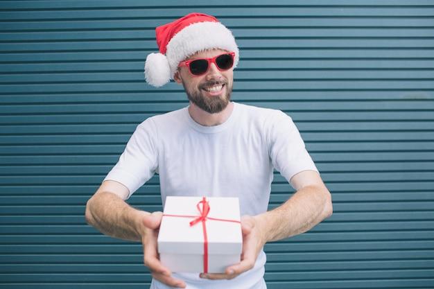 Bebaarde en gelukkige man staat en kijkt op camera. hij draagt een kerstmuts en een bril. de mens lacht. guy houdt aanwezig in handen. geïsoleerd op gestreept