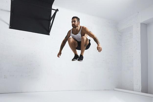 Bebaarde en getatoeëerde jonge mannelijke atleet toont gymnastiekbewegingen hoge sprongen in de lucht, geïsoleerd in witte kamer van fitnesscentrum