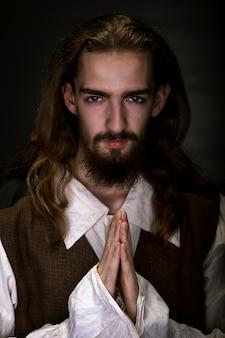 Bebaarde en harige man verkleed als middeleeuwse boer die op zwarte muur bidt