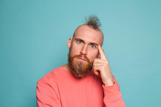 Bebaarde europese man in casual perzik geïsoleerd, bezorgd over een vraag, bezorgd en nerveus