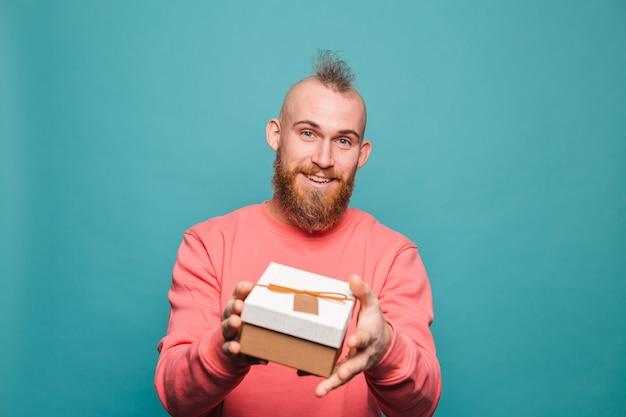 Bebaarde europese man in casual perzik geïsoleerd, gelukkig houdt geschenkdoos