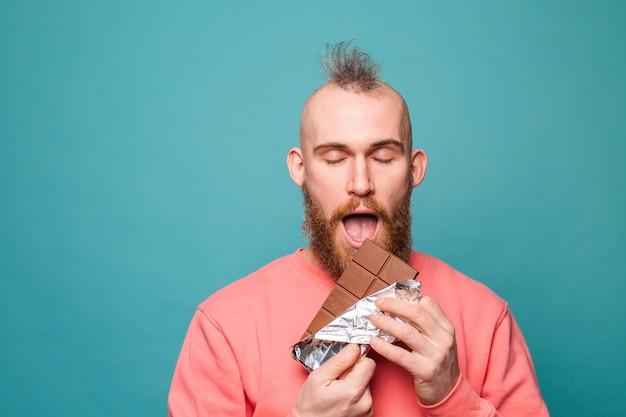 Bebaarde europese man in casual perzik geïsoleerd, genieten van chocolade met gesloten ogen stuk bijten