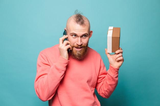 Bebaarde europese man in casual perzik geïsoleerd, geschenkdoos praten op mobiele telefoon schudden doos te houden