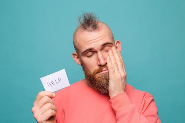Bebaarde europese man in casual perzik geïsoleerd, houdt papier met helpteken triest ongelukkig smeekt