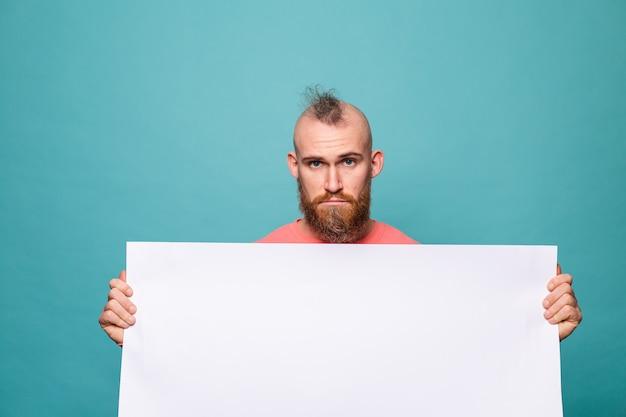 Bebaarde europese man in casual perzik geïsoleerd, met witte lege kartonnen bord met droevig ongelukkig gezicht
