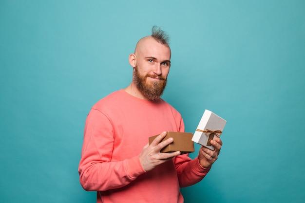 Bebaarde europese man in casual perzik geïsoleerd, opgewonden opening geschenkdoos