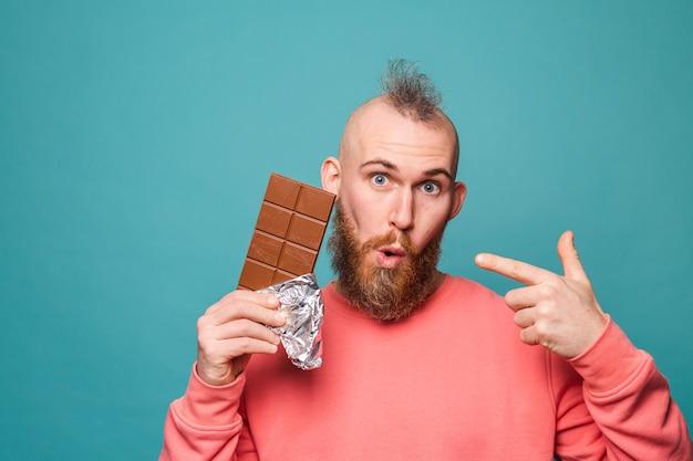 Bebaarde europese man in casual perzik geïsoleerd, opgewonden verbaasd punt op chocolade