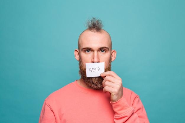Bebaarde europese man in casual perzik geïsoleerd, papier met help teken brutaal met ernstig gezicht te houden