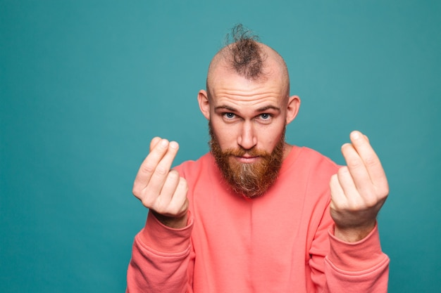 Bebaarde europese man in casual perzik geïsoleerd, vingers wrijven geld gebaar doen