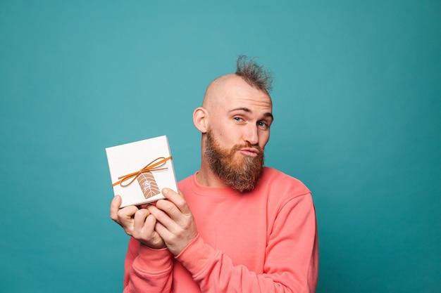 Bebaarde europese man in casual perzik geïsoleerde, opgewonden vrolijke bedrijf geschenkdoos