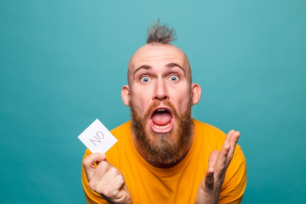 Bebaarde europese man in geel overhemd geïsoleerd, geen schreeuwen boos geschokt houden