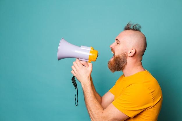 Bebaarde europese man in geel overhemd geïsoleerd, gek geschreeuw in megafoonluidspreker, opgelet!