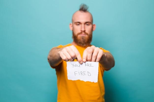 Bebaarde europese man in geel overhemd geïsoleerd, papier met je vasthoudend, scheurt het papier van woede