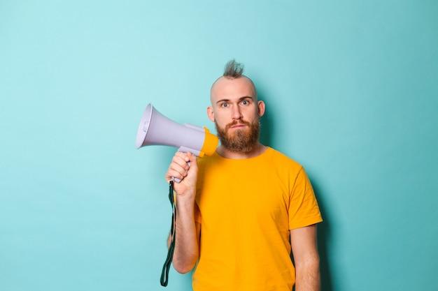 Bebaarde europese man in geel shirt geïsoleerd, megafoon te houden