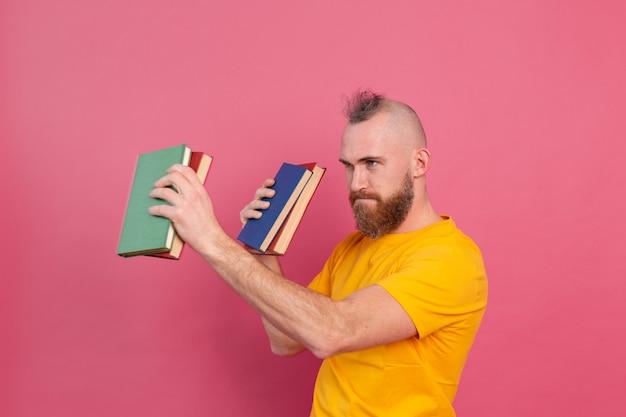 Bebaarde europese man met stapel boeken op roze