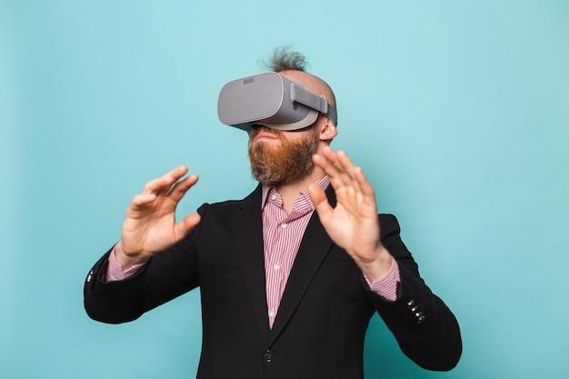 Bebaarde europese zakenman in donker pak geïsoleerd, opgewonden verbaasd aanrakingslucht met virtual reality-bril
