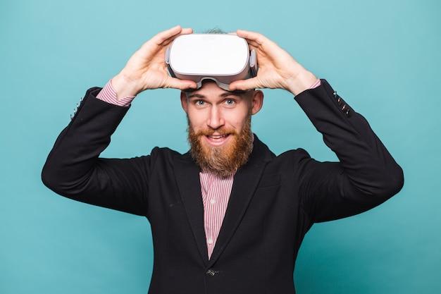 Bebaarde europese zakenman in donker pak geïsoleerd, vr-bril op hoofd met opgewonden blij gezicht