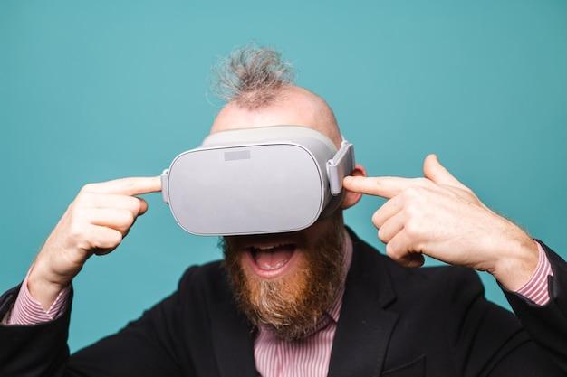Bebaarde europese zakenman in donker pak geïsoleerd, vr-bril op hoofd met opgewonden verbaasd geschokt gezicht open mond
