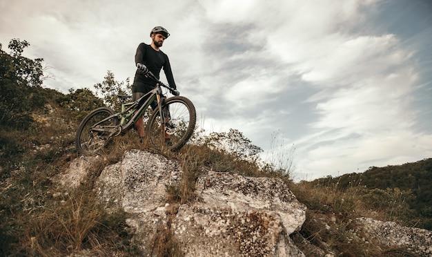 Bebaarde fietser met fiets die heuvelafwaarts loopt