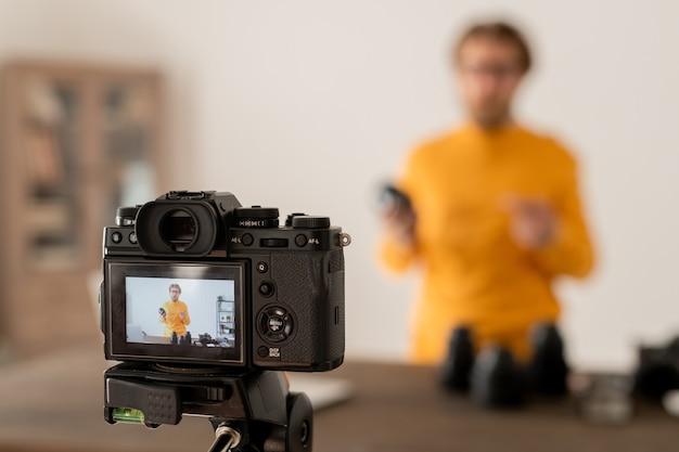 Bebaarde fotograaf die onderdelen van een nieuw model van professionele fotocamera toont aan zijn online publiek tijdens de les